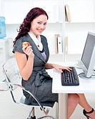 Young businesswoman holding an apple in office