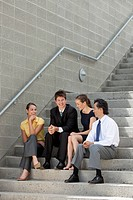 Businesspeople sit together on steps and having a conversation.