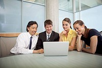 Group of businesspeople looking at a laptop together.