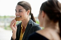 Businesswoman smiles while eating a cookie outdoors.