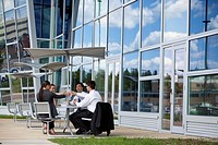 Four businesspeople sit outside an office building for lunch.