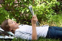 Young girl lies in the grass outdoors and reads from a notebook.