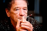 Senior man holding small hypodermic needle
