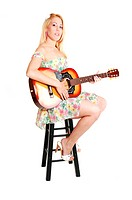 A beautiful woman sitting and playing the guitar in a light colorful short top and skirt , for white background.