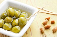 the green olives in ceramic bowl on old table