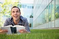 Man smiles as he reads on a college campus lawn.