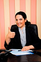 Elegant business woman sittiing on chair at desktop in her office and giving thumbs up