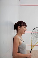 Woman with a racquet on a racquetball court.