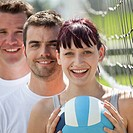 Group of friends stand and smile while holding a volleyball.