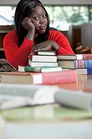 Woman at a library table leans on a stack of books while looking at the camera.