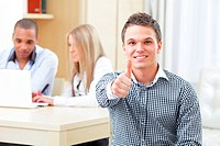 Cheerful bisnessman showing thumbs up, his business team on the background