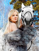 outdoor portrait of beautiful blonde girl in furs with pale horse in sunny winter forest