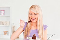 Beautiful caucasian woman eating cake in the kitchen