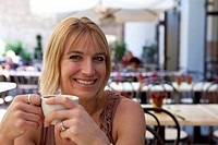 Attractive blond woman drinking coffee in cafe