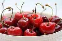 A group of juicy, fresh cherries in a white bowl