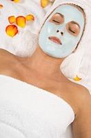 Young beautiful woman relaxing with moistening facial mask