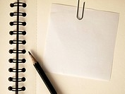 Note paper clip on notebook and black pencil