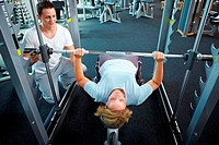 Woman lifting weights with personal trainer in a gym