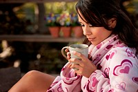 Pretty Hispanic Woman in Bathrobe Sitting Outdoors with Tea