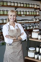 Portrait of a happy senior woman with arms crossed in spice store