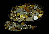 Various coins in a basket on black background