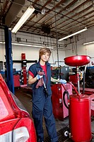 Portrait of a young mechanic standing by welding equipment