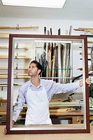 Young craftsman looking on frame´s corner in workshop