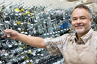 Portrait of a happy mature salesperson holding metallic equipment in hardware store