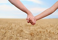 Young couple holding hands in the field. Close_up