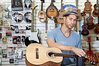 Portrait of a confident man restringing guitar in music store