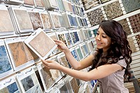 Happy young store clerk arranging samples in display