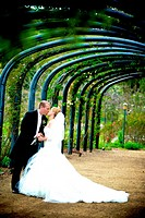 kissing under a canopy of garden arches