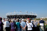 England, London, Stratford. Tourists viewing the Olympic Stadium in Olympic Park.