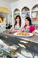 Happy caterers with pastry tray looking away in cake shop
