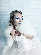 Woman as a snow queen in ice room