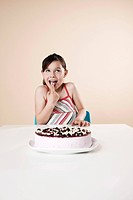 Girl sitting at table with gateau