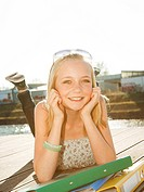 Smiling teenage girl lying on jetty