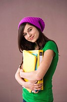 Teenage girl with woolen hat holding folders