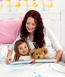 Mother and daughter reading a book together in bed