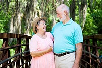 Senior couple laughing together in a beautiful natural setting.