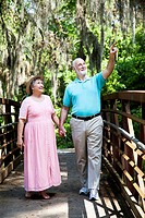Senior couple on vacation in Florida walking through a tropical park.