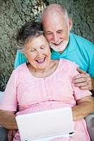 Senior couple stays in touch with the grandchildren using a small netbook laptop computer.