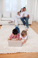 Brother and sister using a laptop on floor in living_room with their parents on sofa