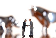 Two manager figurines shaking hands, with bull and bear out of focus behind them, symbolic image for stock exchange business
