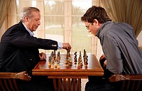 Mature man and younger man playing chess (thumbnail)