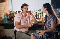 Couple in a bar, man lighting cigar