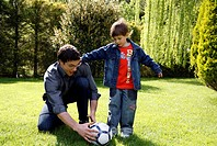 Man teaching boy to play soccer (thumbnail)