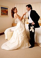 Bride and groom undressing in hotel room
