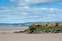 View of coast with rocky outcrop at low tide, looking towards Grange_over_sands, Silverdale, Morecambe Bay, Lancashire, England, april