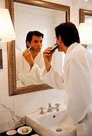 Man shaving in the bathroom mirror